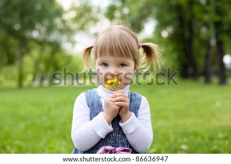 Portrait of a happy little girl in the park - stock photo