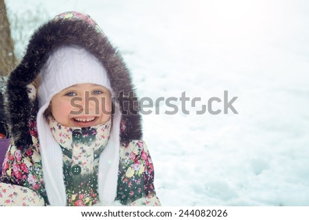 Portrait of a happy little girl in the snow - stock photo