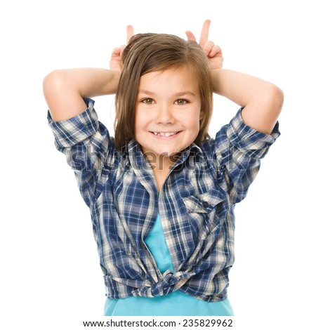 Portrait of a happy little girl laughing and making horns or bunny ears, isolated over white - stock photo