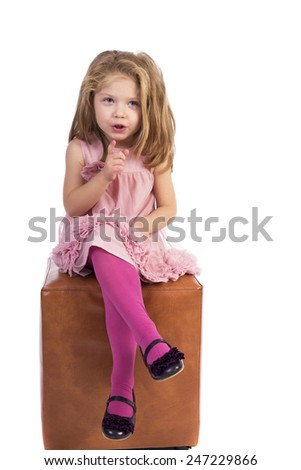 Portrait of a happy little girl pointing over white background - stock photo