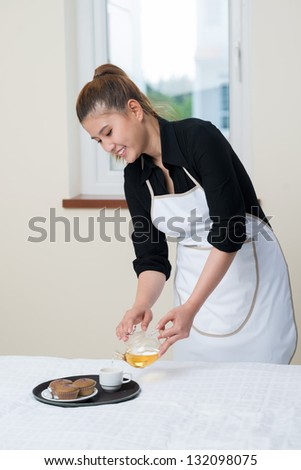 Portrait of a happy maid preparing breakfast