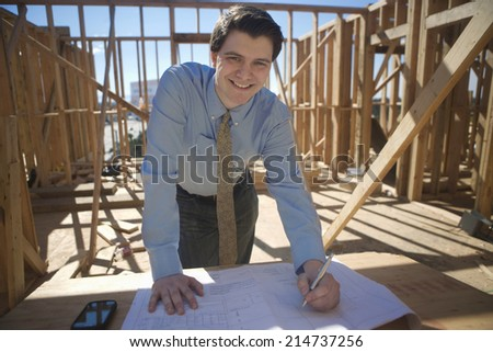 Portrait of a happy male architect working on blueprint at construction site - stock photo