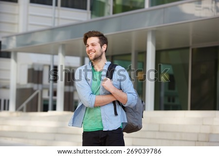 Portrait of a happy male college student standing outside with bag