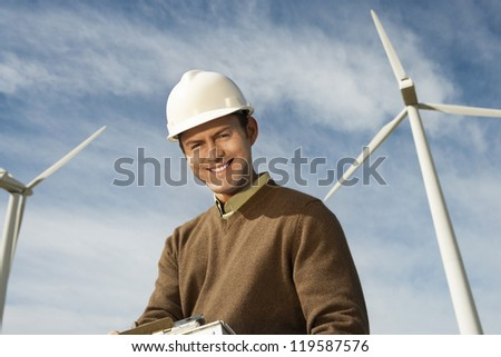Portrait of a happy male engineer against wind turbine and cloudy sky - stock photo