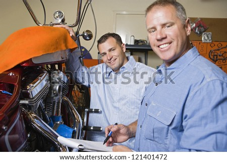 Portrait of a happy male mechanic with his client in garage