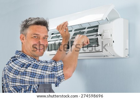 Portrait Of A Happy Male Technician Repairing Air Conditioner - stock photo