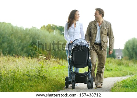 Portrait of a happy man and woman walking with baby pram outdoors