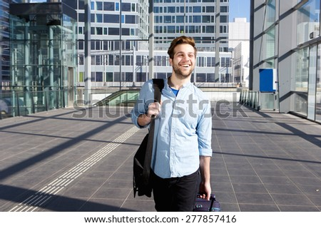 Portrait of a happy man at airport leaving for vacation - stock photo