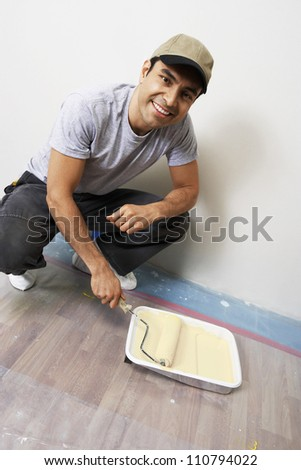 Portrait of a happy man holding paint roller - stock photo