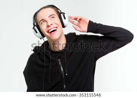 Portrait of a happy man listening music in headphones and looking up isolated on a white background