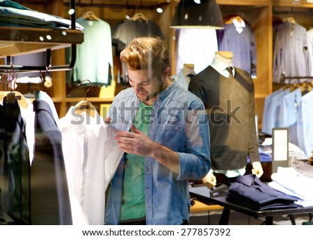 Portrait of a happy man shopping for clothes at clothing store