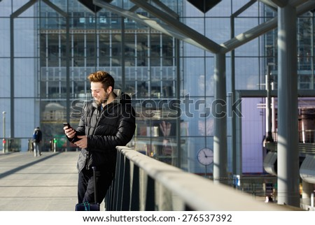 Portrait of a happy man waiting at station and looking at mobile phone - stock photo