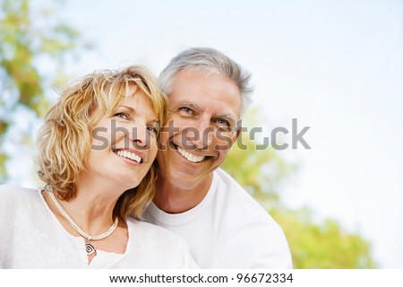 Portrait of a happy mature couple outdoors. Shallow DoF with focus on woman. - stock photo
