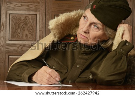 Portrait of a happy mature female soldier writing letter - stock photo