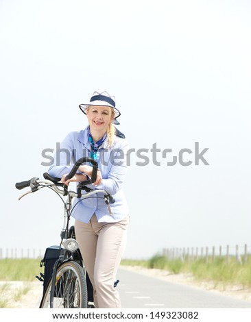 Portrait of a happy mature woman relaxing with bike on a summer day - stock photo