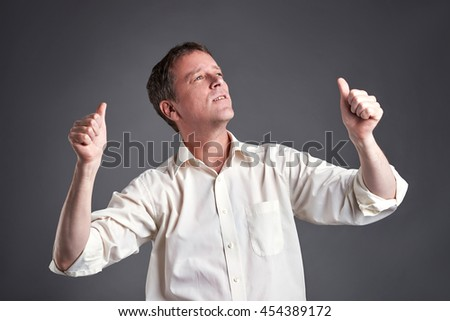 Portrait of a happy middle age man showing thumbs up and celebrating