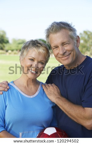 Portrait of a happy middle aged Caucasian couple with football in the park - stock photo