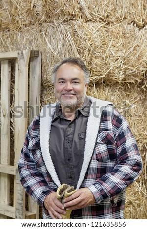 Portrait of a happy middle-aged man in front of hay stack