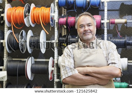 Portrait of a happy middle-aged salesperson standing in front of electrical wire spool with arms crossed in hardware store - stock photo