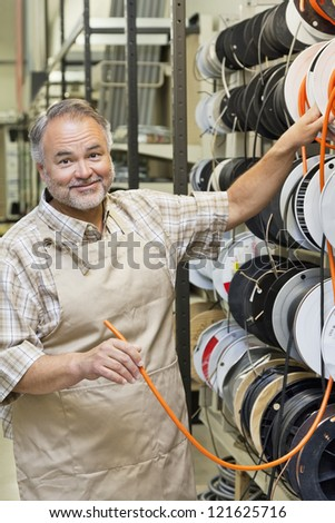 Portrait of a happy middle-aged store clerk with electrical wire spool in hardware shop - stock photo