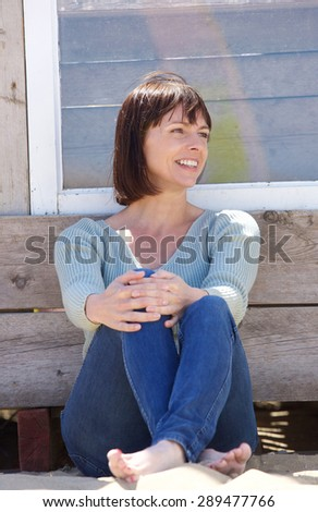 Portrait of a happy middle aged woman in jeans sitting outside - stock photo