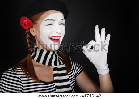 Portrait of a happy mime comedian showing OK, on black background