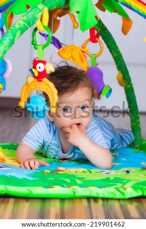 Portrait of a happy 6 months old baby boy at tummy time on the play gym. - stock photo