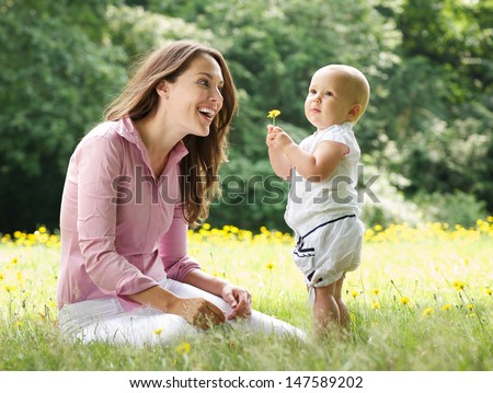 Portrait of a happy mother and child in the park - stock photo