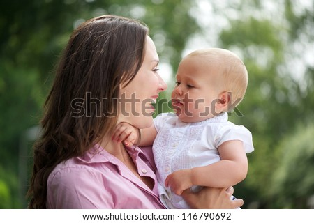Portrait of a happy mother and cute baby looking at each other - stock photo