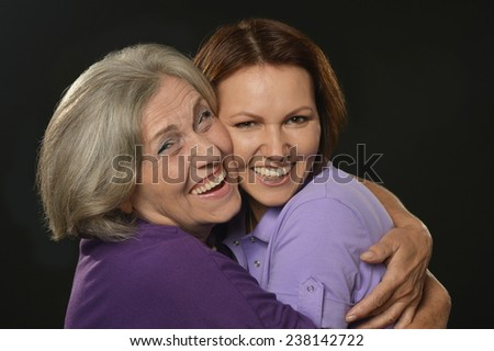 Portrait of a happy mother and daughter on black - stock photo