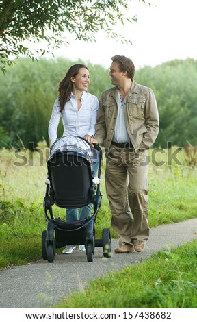 Portrait of a happy mother and father pushing baby pram outdoors