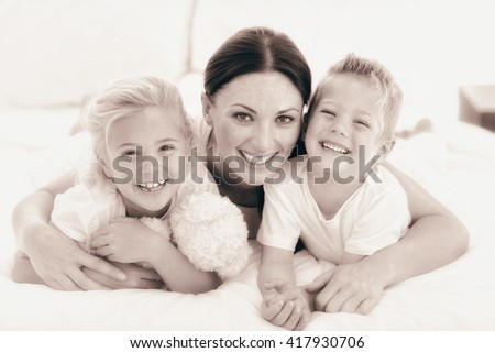 Portrait of a happy mother and her children lying on a bed