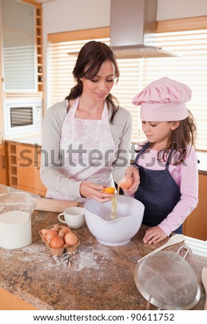Portrait of a happy mother and her daughter baking in a kitchen - stock photo