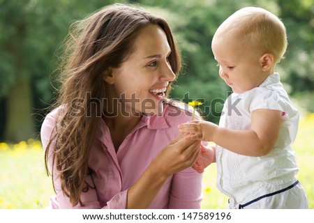 Portrait of a happy mother giving flower to baby in the park - stock photo