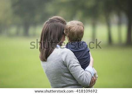 Portrait of a happy Mother holding son outdoors. Love and togetherness concept. - stock photo