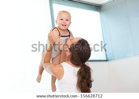 Portrait of a happy mother lifting up cute baby at home