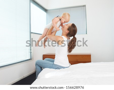 Portrait of a happy mother playing with baby in bedroom