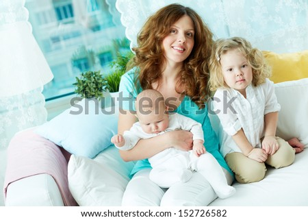 Portrait of a happy mother resting with her two kids at home - stock photo
