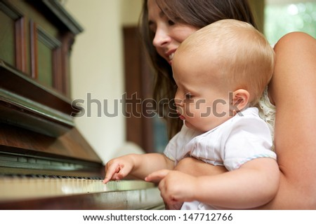 Portrait of a happy mother teaching cute baby to play piano - stock photo