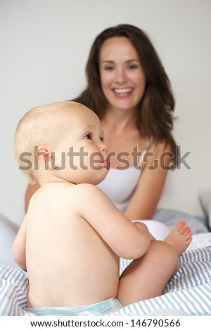 Portrait of a happy mother with baby on bed - stock photo
