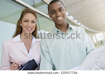 Portrait of a happy multi ethnic business people with blue print - stock photo