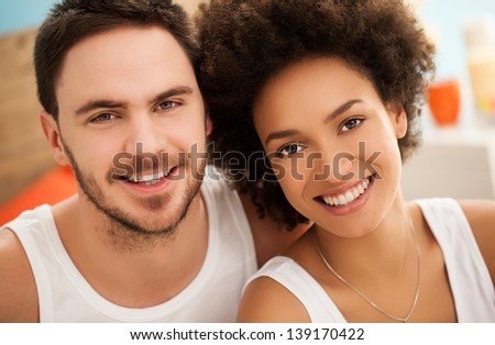 Portrait of a happy multiethnic couple in their bedroom. - stock photo