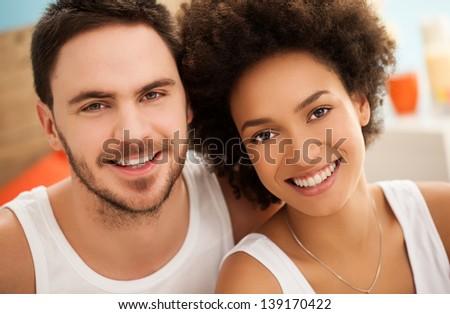Portrait of a happy multiethnic couple in their bedroom. - stock photo