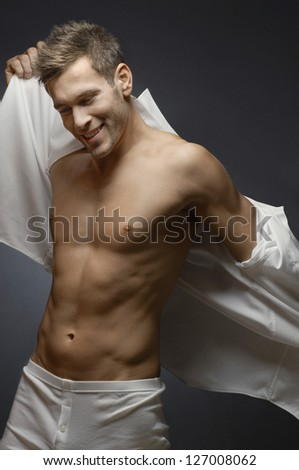 Portrait of a happy muscular man removing his shirt isolated over grey background