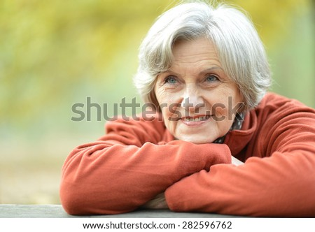portrait of a happy old woman posing at nature - stock photo