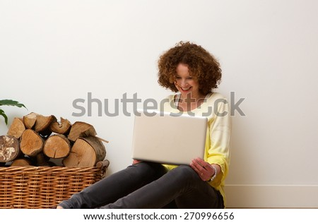 Portrait of a happy older woman using laptop oat home - stock photo
