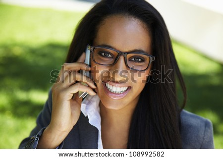 Portrait of a happy Phone african businesswoman - outdoors - stock photo
