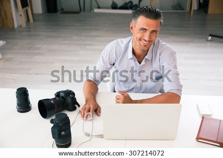 Portrait of a happy photographer using laptop at his workplace and looking at camera - stock photo