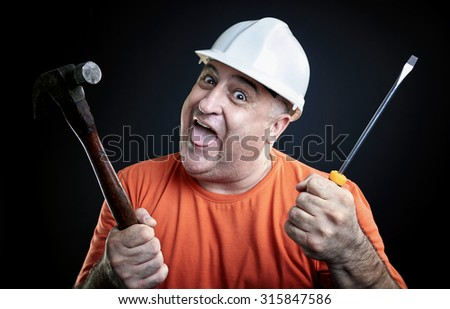 Portrait of a happy repairman wearing safety equipment holding hammer and screwdriver. Industry equipment concept. - stock photo