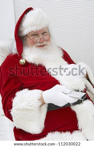 Portrait of a happy Santa Clause watching television